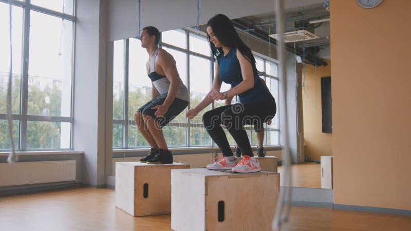 La mujer joven juguetona y el instructor muscular de la aptitud del hombre que hacen la caja saltan ejercicio durante un entrenam imágenes de archivo libres de regalías