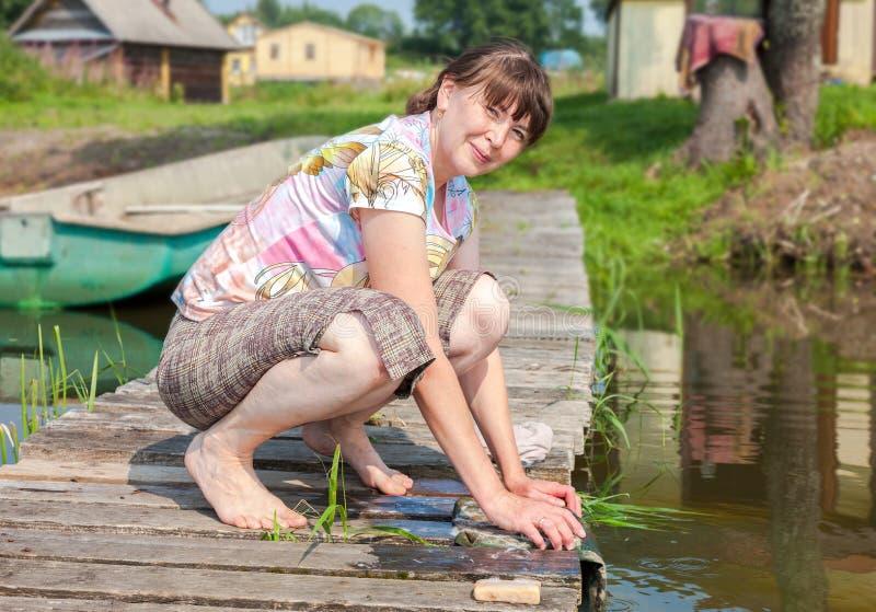 La mujer joven lava la ropa en el embarcadero de madera por el lago en verano fotos de archivo