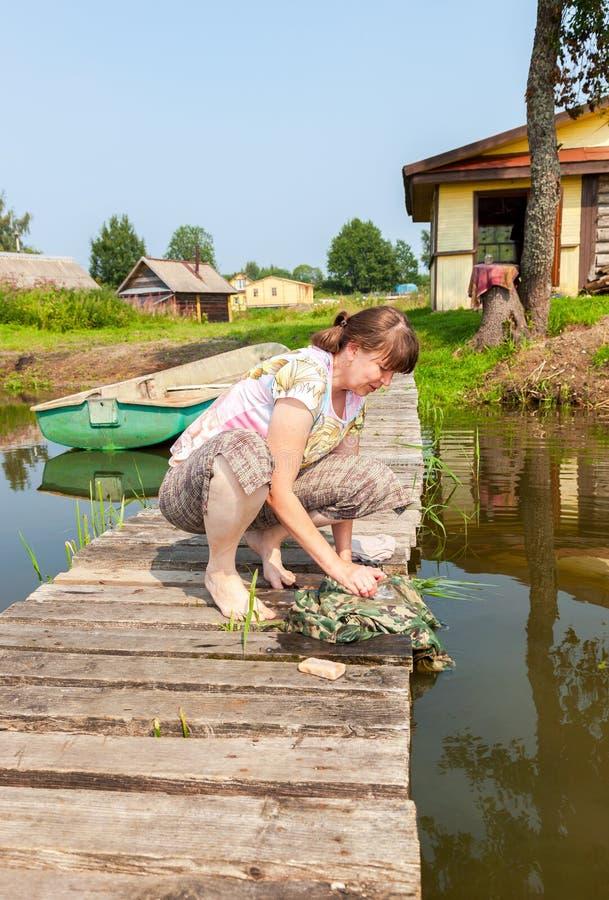 La mujer joven lava la ropa en el embarcadero de madera por el lago en verano fotografía de archivo