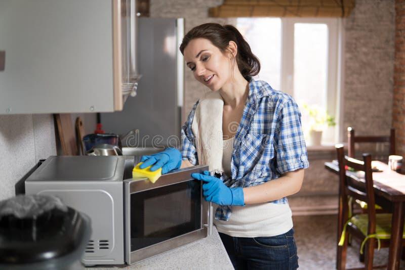 La mujer joven lava una microonda fotografía de archivo libre de regalías