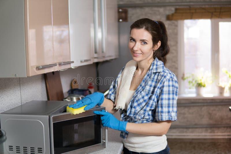 La mujer joven lava una microonda fotos de archivo libres de regalías