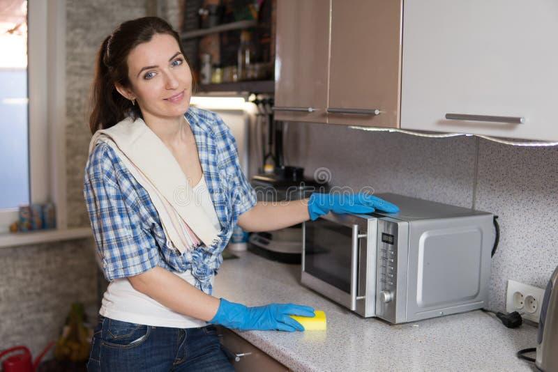 La mujer joven lava una microonda imagen de archivo
