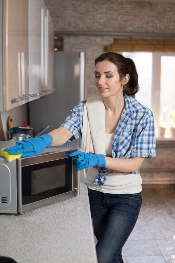 La mujer joven lava una microonda fotografía de archivo