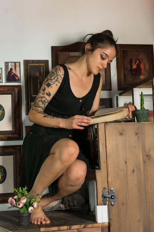 La mujer joven lee adentro su estudio de pintura imagen de archivo