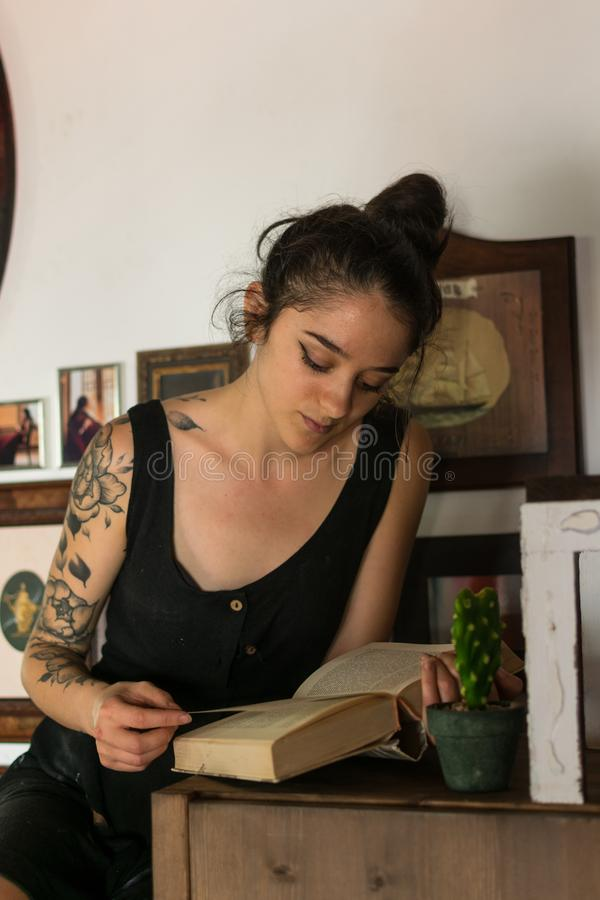 La mujer joven lee adentro su estudio de pintura fotografía de archivo