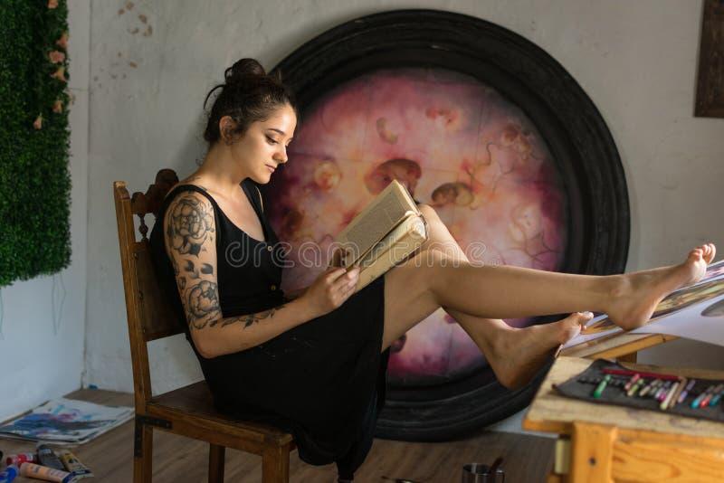 La mujer joven lee adentro su estudio de pintura fotos de archivo