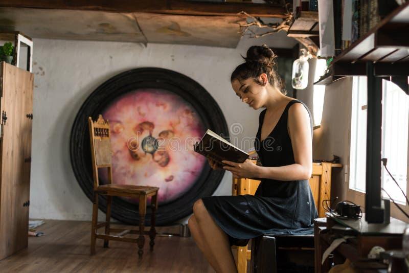 La mujer joven lee adentro su estudio de pintura imagen de archivo libre de regalías