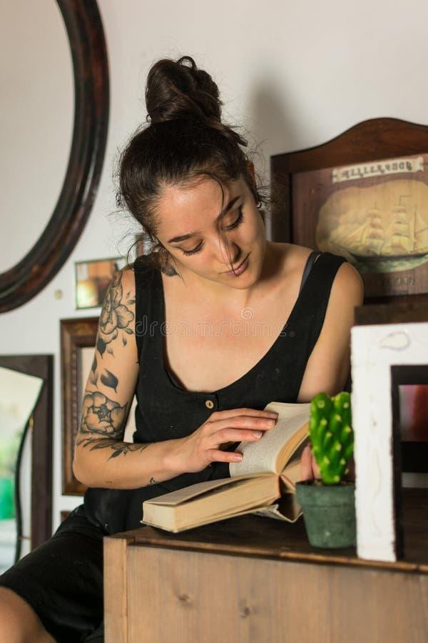 La mujer joven lee adentro su estudio de pintura foto de archivo libre de regalías