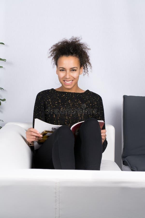 La mujer joven lee una revista fotografía de archivo libre de regalías