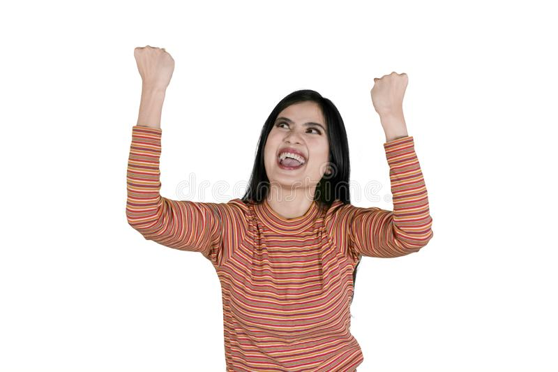 La mujer joven levanta las manos para celebra éxito imagen de archivo