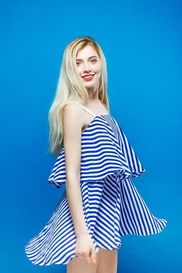 La mujer joven linda está presentando en estudio Retrato del vestido rayado del verano del Blonde que lleva hermoso en fondo azul imágenes de archivo libres de regalías