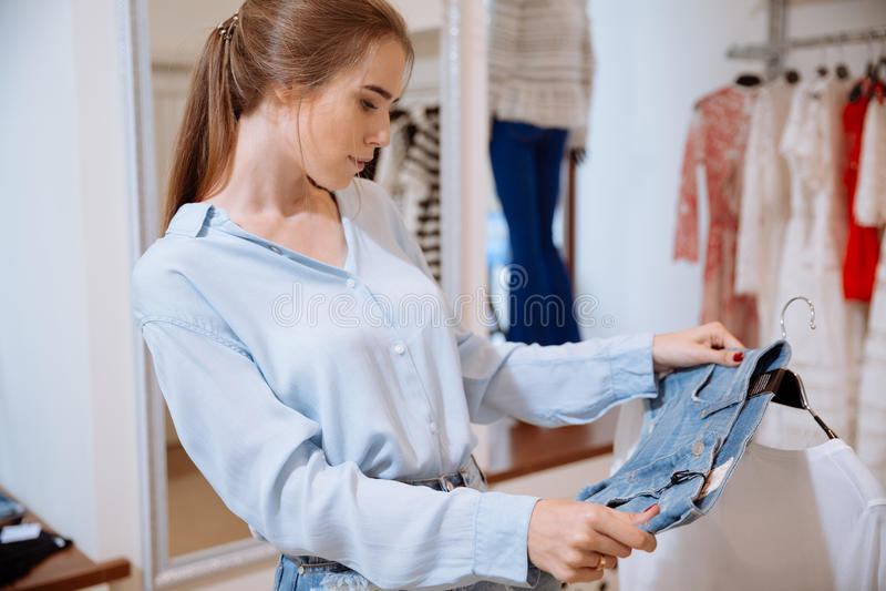 La mujer joven linda que piensa y que elige la ropa en ropa hace compras foto de archivo