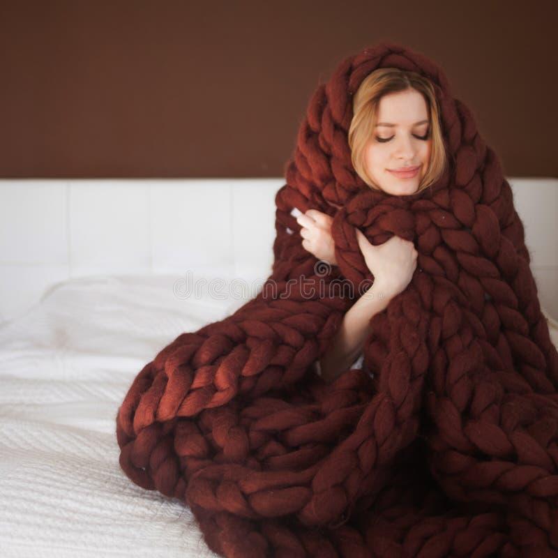 La mujer joven linda se est? sentando en la cama envuelta en una tela escocesa marr?n grande y mullida Calor y comodidad del hoga fotos de archivo