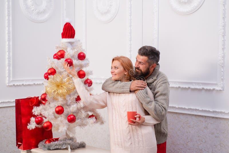 La mujer joven linda y el hombre hermoso celebran Feliz Año Nuevo El par feliz sobre el árbol de navidad enciende el fondo fotos de archivo libres de regalías