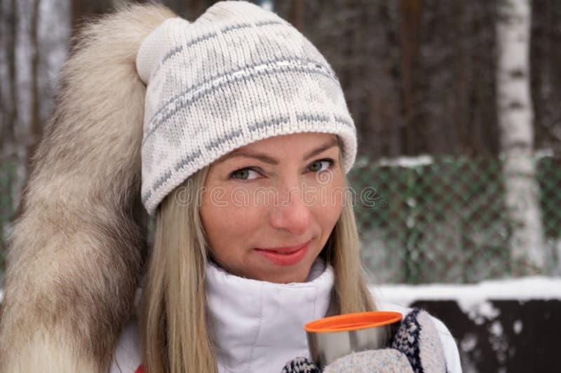 La mujer joven lleva a cabo en su mano una taza de aire libre del casquillo del termo del té en un día escarchado foto de archivo