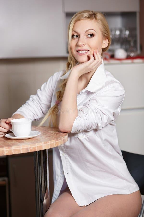 La mujer joven lleva a cabo una taza de coffe imagenes de archivo