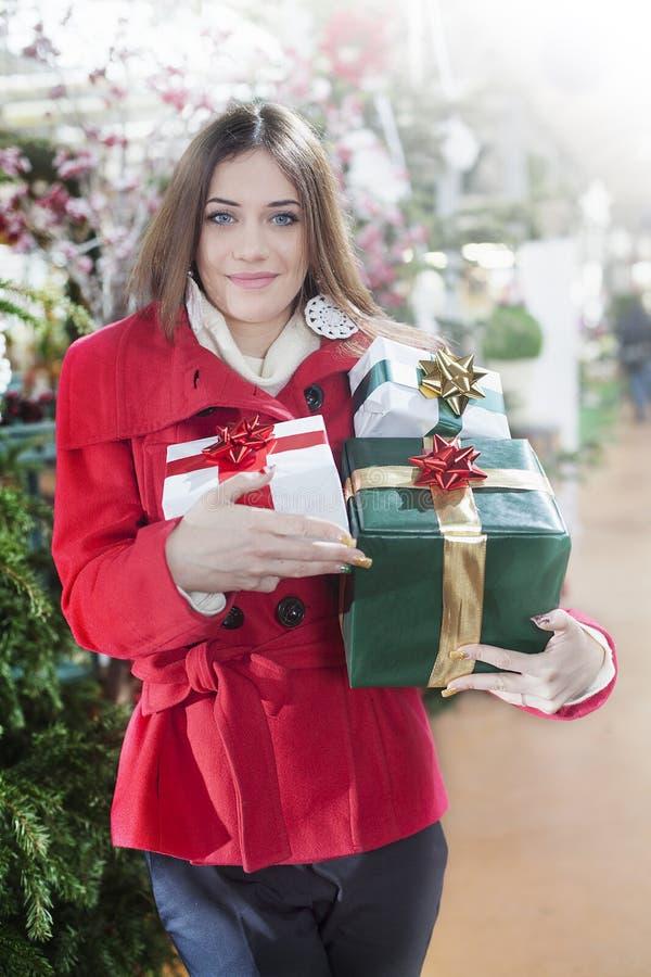 La mujer joven lleva sus regalos de la Navidad imagen de archivo libre de regalías
