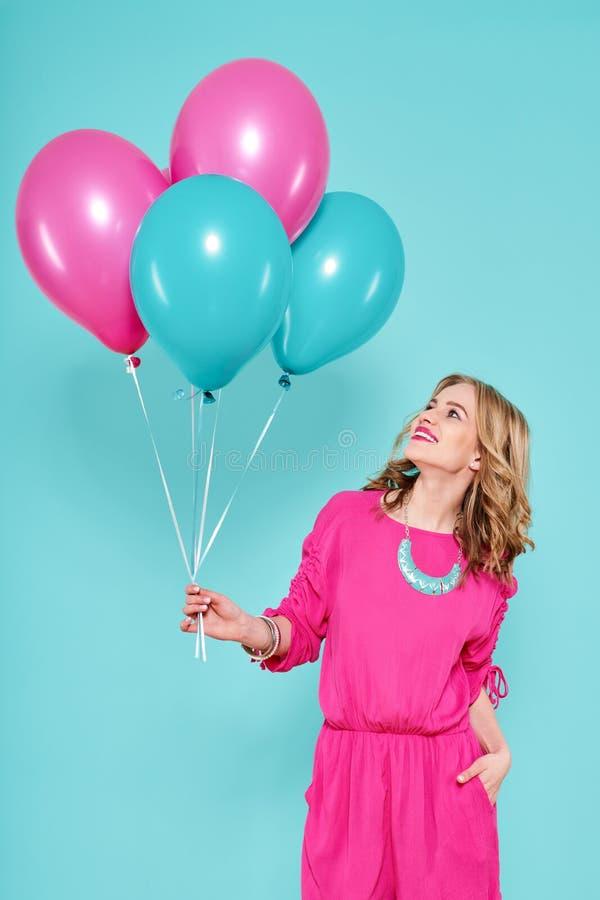 La mujer joven magnífica en el vestido del verano del partido que sostenía el manojo de globos coloridos, aislado sobre azul en c foto de archivo