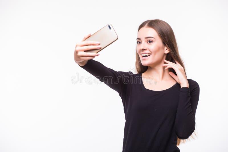 La mujer joven magnífica en estilo de la calle viste tomar el selfie con el teléfono móvil aislado sobre el fondo blanco fotografía de archivo