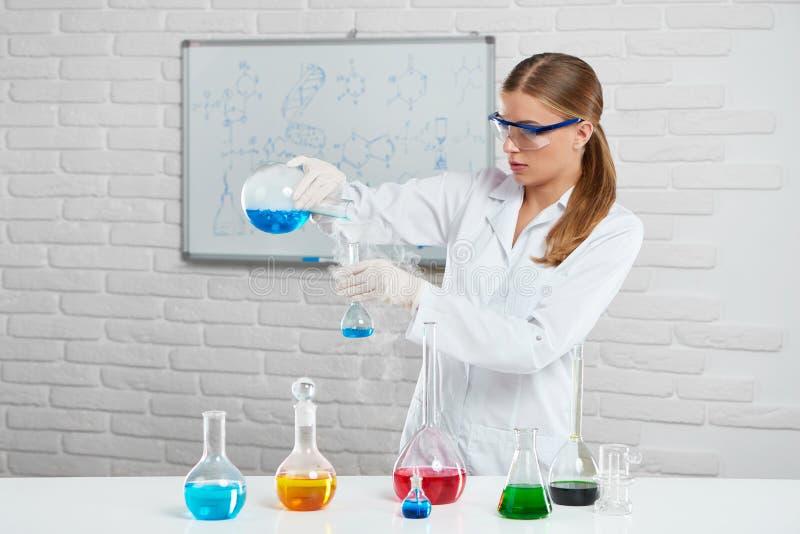La mujer joven mezcla líquidos químicos coloridos fotografía de archivo libre de regalías