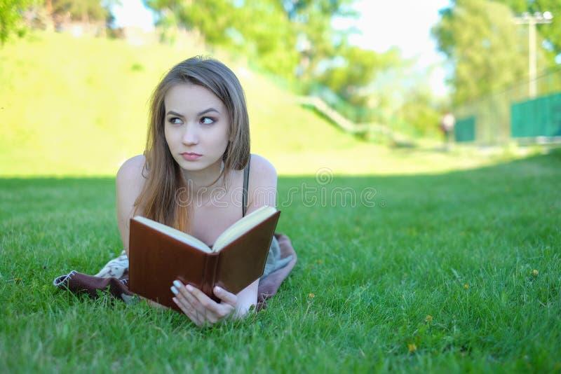 La mujer joven miente en hierba verde y lee el libro en el parque de la ciudad foto de archivo libre de regalías