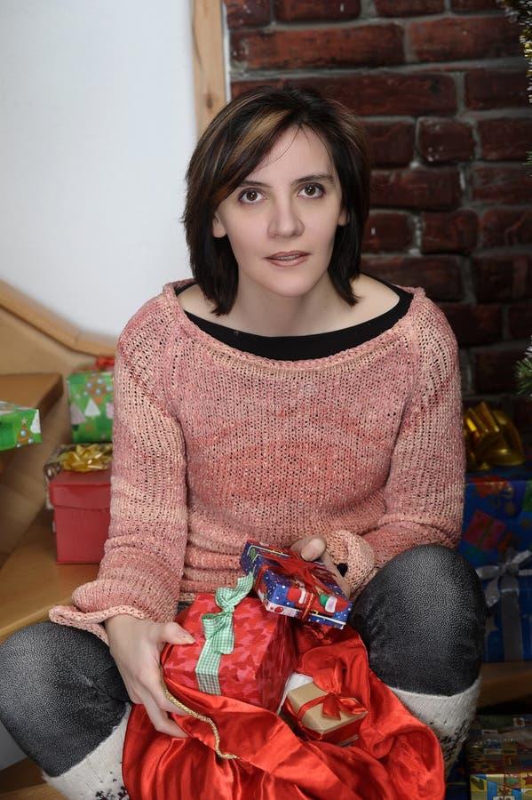 La mujer joven mira el bolso de la Navidad con los regalos foto de archivo libre de regalías