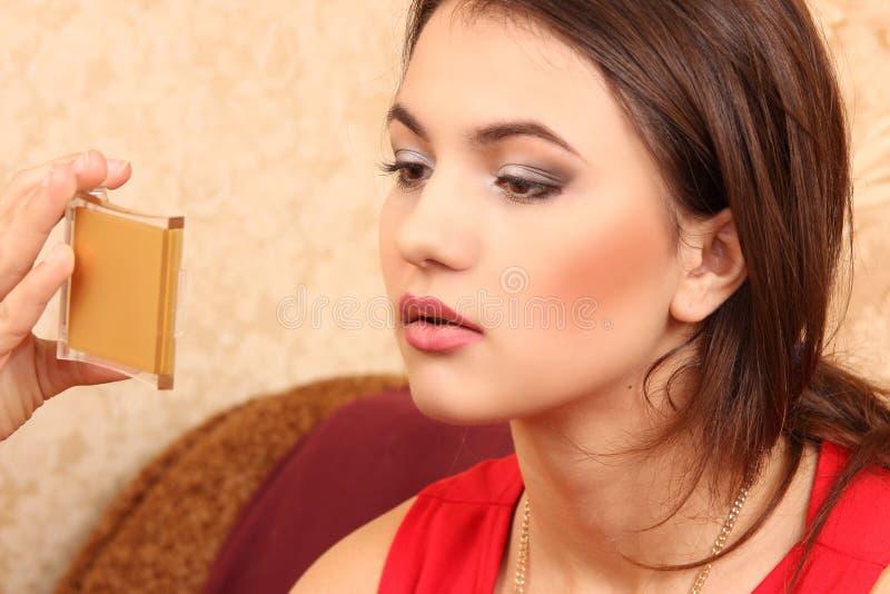 La mujer joven mira en un pequeño espejo cosmético del bolsillo imagen de archivo