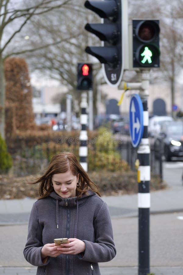 La mujer joven mira su teléfono móvil y no presta la atención a fotos de archivo libres de regalías