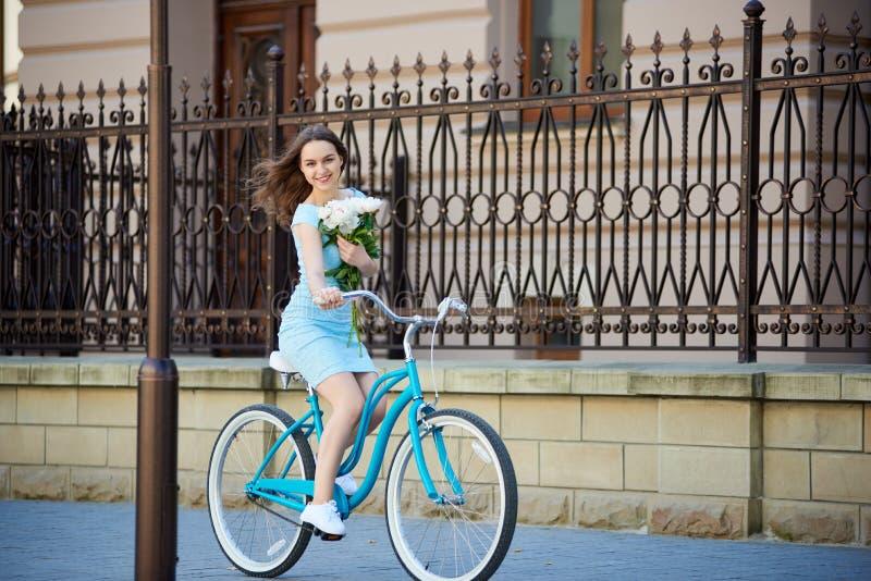 La mujer joven monta en la bici retra que sostiene sus peonías fotos de archivo libres de regalías