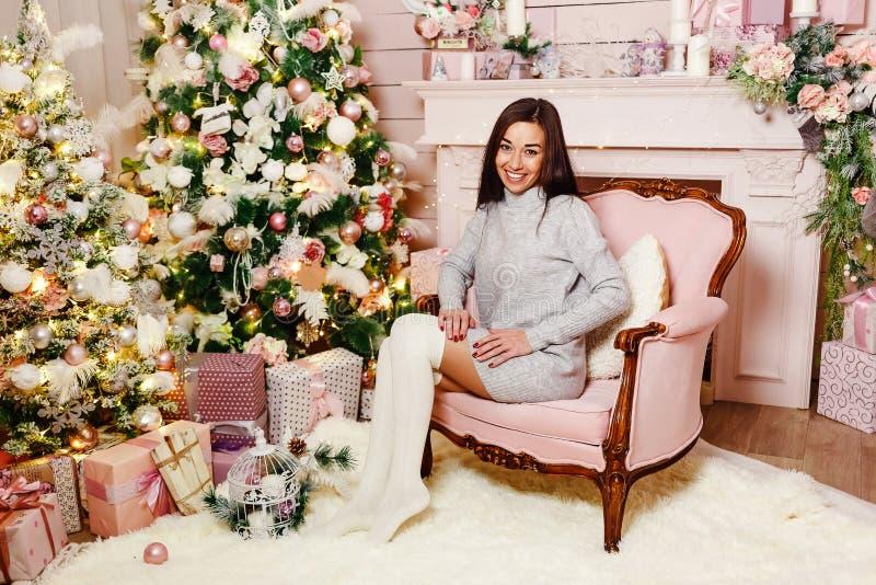 La mujer joven morena se sienta en una silla cerca de un árbol de navidad fotografía de archivo