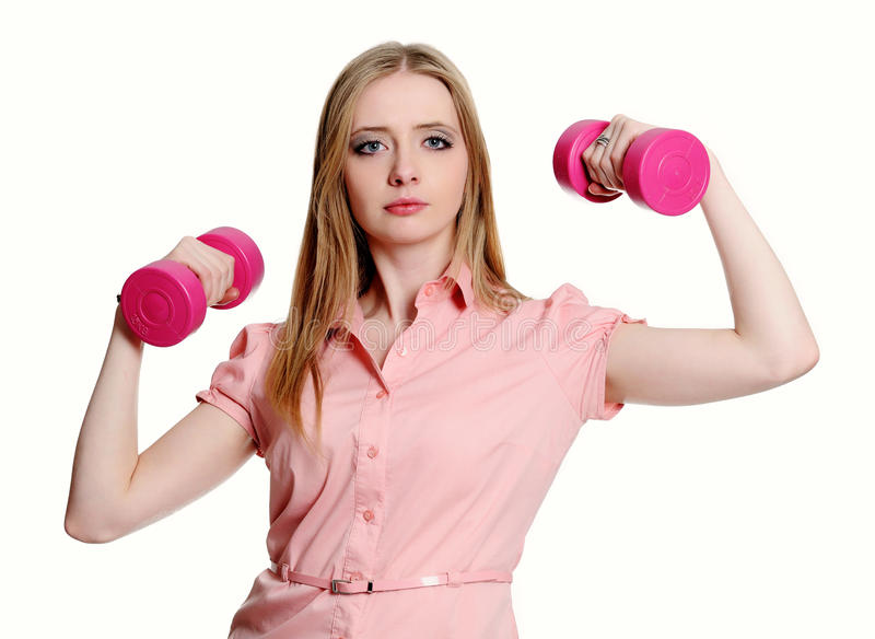 La mujer joven muestra sus fuerzas que llevan a cabo pesa de gimnasia fotografía de archivo