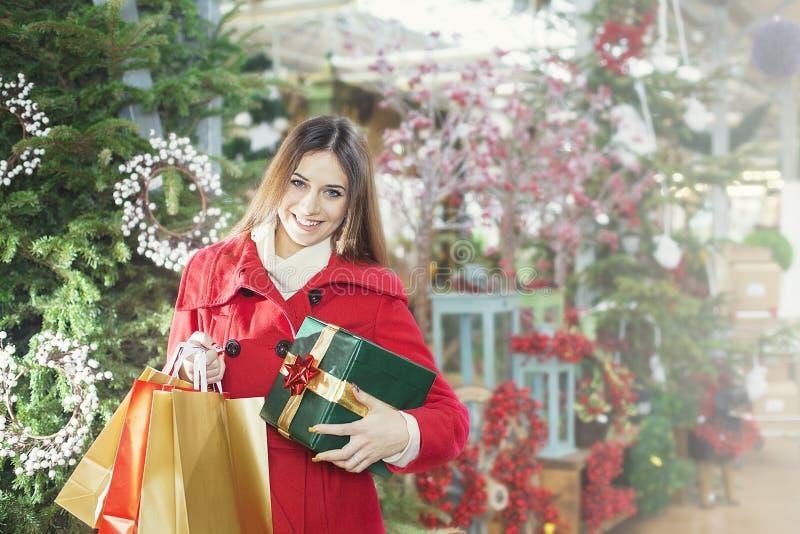 La mujer joven muestra sus paquetes del regalo dentro de una tienda de la Navidad fotografía de archivo libre de regalías