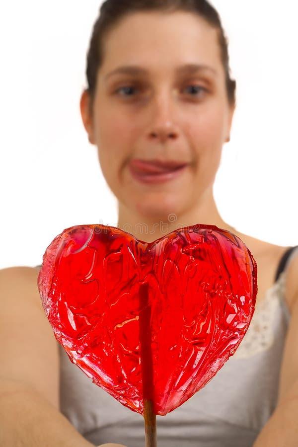 La mujer joven no puede esperar para lamer el lollipop foto de archivo libre de regalías