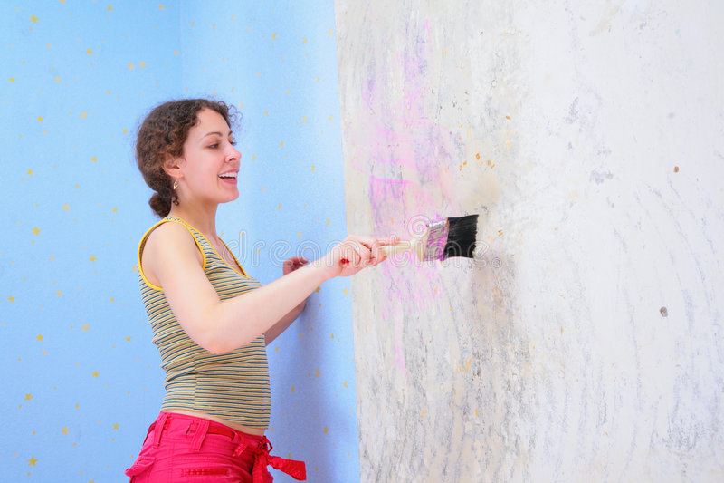 La mujer joven pega el papel pintado foto de archivo