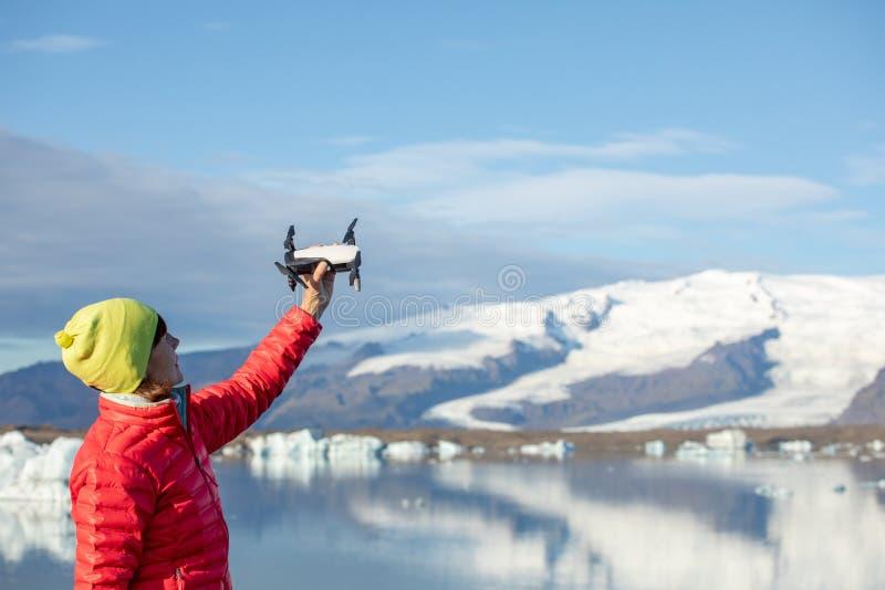 La mujer joven pone en marcha el quadcopter Mujer con el artilugio en un fondo de montañas y del hielo azules hermosos fotografía de archivo libre de regalías