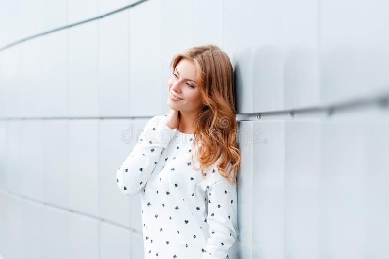 La mujer joven positiva europea linda en ropa de moda es permanente y sonriente cerca de la pared moderna blanca dentro imagen de archivo