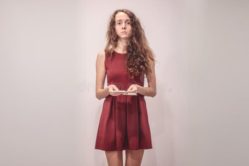 La mujer joven preocupante en vestido rojo se sostiene en la cabeza fotografía de archivo libre de regalías