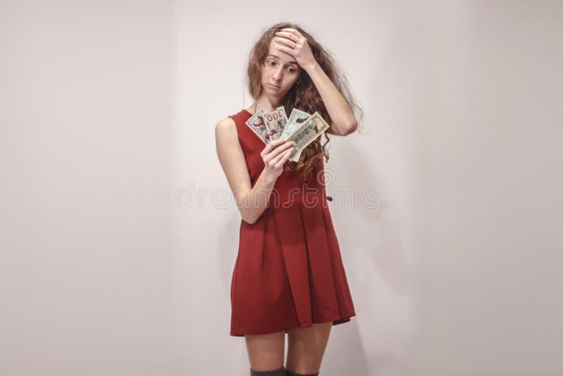 La mujer joven preocupante en vestido rojo se sostiene en la cabeza foto de archivo