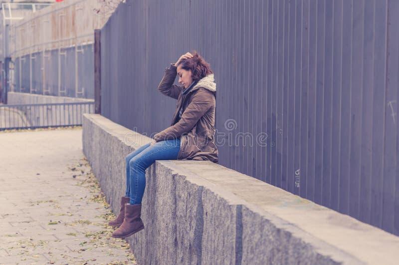La mujer joven presionada que se sentaba en la calle urbana de la ciudad abrum? a fotos de archivo