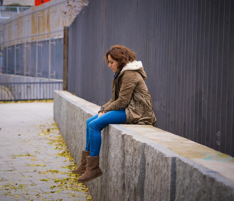 La mujer joven presionada que se sentaba en la calle urbana de la ciudad abrum? a foto de archivo libre de regalías
