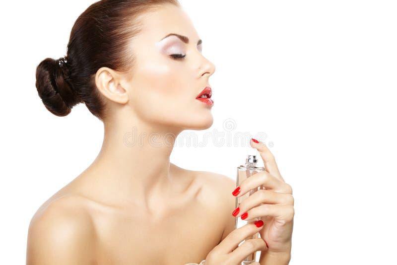 La mujer joven que aplicaba perfume en sí misma aisló en el backgr blanco imagen de archivo libre de regalías