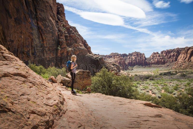 La mujer joven que camina en barranco rojo hermoso de la roca con un escénico pasa por alto imagen de archivo