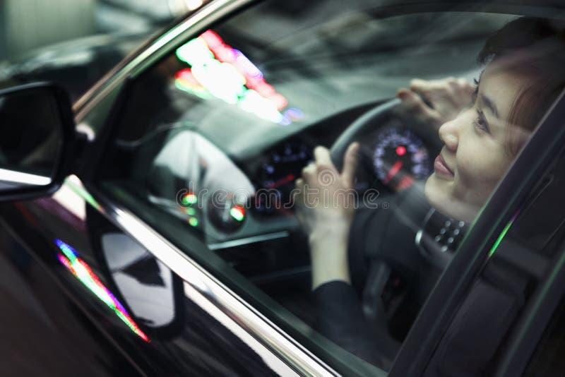 La mujer joven que conduce y que considera a través de la ventanilla del coche la noche de la ciudad se enciende fotografía de archivo