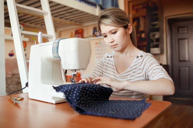 La mujer joven que cose con cose la máquina en casa mientras que se sienta por su lugar de trabajo El crear del diseñador de moda imagen de archivo