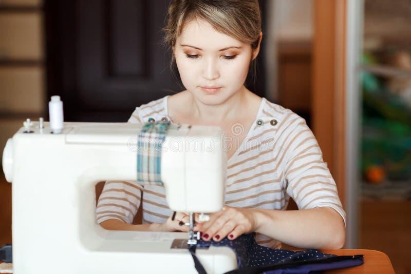 La mujer joven que cose con cose la máquina en casa mientras que se sienta por su lugar de trabajo El crear del diseñador de moda fotografía de archivo