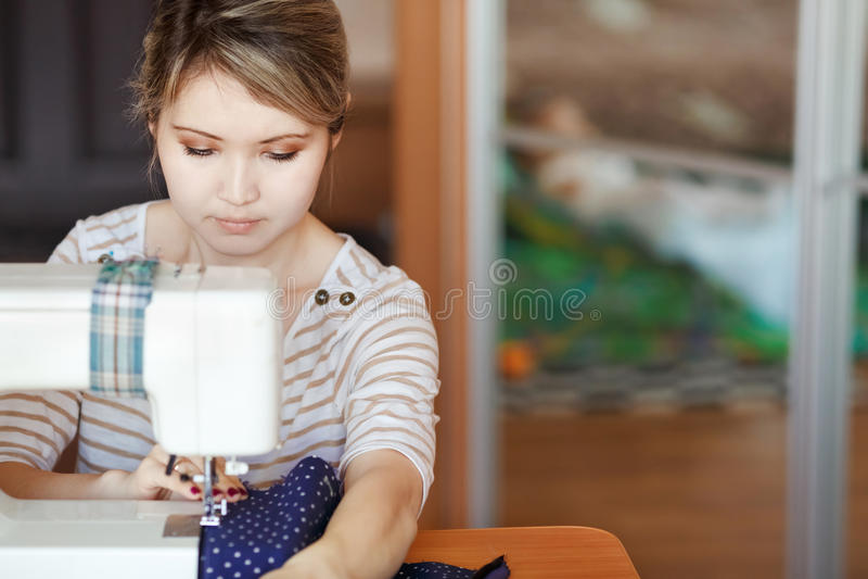La mujer joven que cose con cose la máquina en casa mientras que se sienta por su lugar de trabajo El crear del diseñador de moda foto de archivo libre de regalías