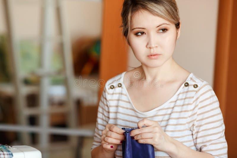 La mujer joven que cose en casa, dobladillando la tela azul, se coloca y mira pensativamente al lado Copie el espacio El crear de fotos de archivo