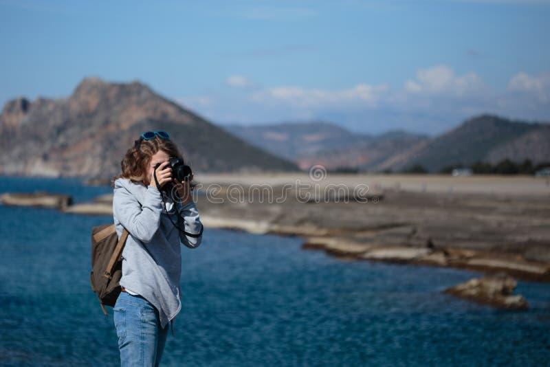 La mujer joven que fotografiaba la roca proveyó de costillas la playa de Koru en el Al de Gazipasha imagen de archivo libre de regalías
