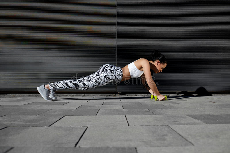 La mujer joven que hace la prensa sube con pesas de gimnasia mientras que se coloca en fondo negro al aire libre foto de archivo libre de regalías