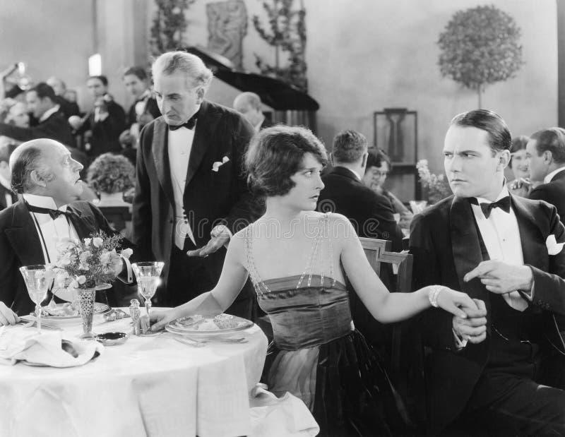 La mujer joven que lleva a cabo la mano de un hombre en una diversa tabla mientras que su compañero está hablando con el camarero imagen de archivo